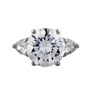 Round brilliant diamond engagement ring with pear shaped side stones