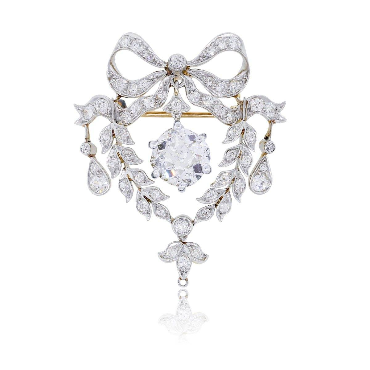 This amazing antique diamond brooch features a true cushion cut diamond center.