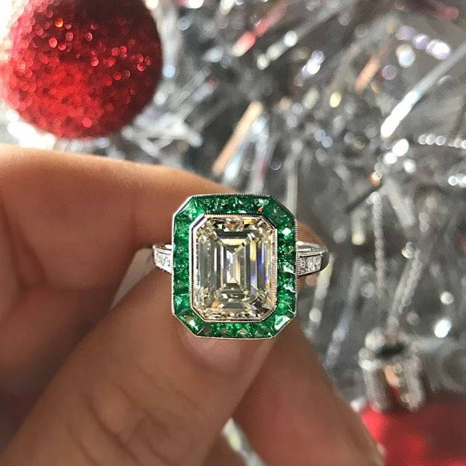 An emerald colored engagement wedding ring behind holiday decorations.