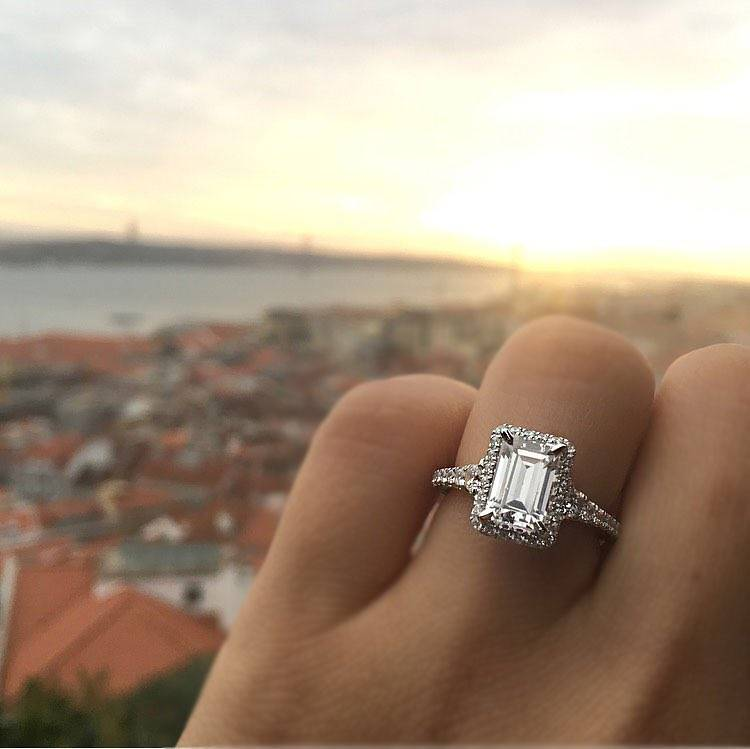 An engagement ring showcased behind a scenic background.
