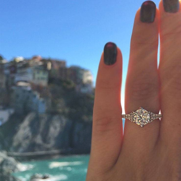 An engagement wedding ring showcased behind a scenic background.