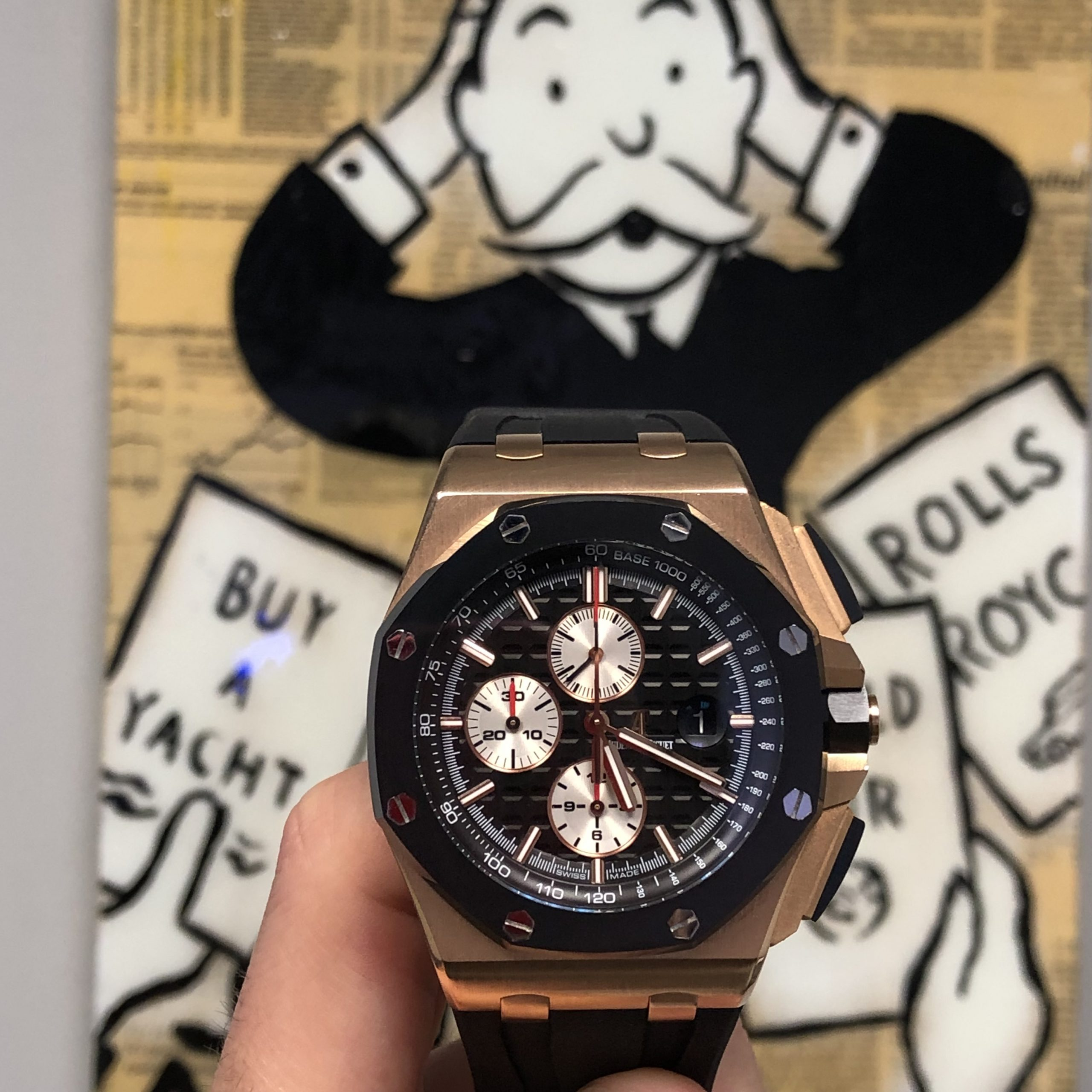 audemars piguet royal oak offshore rose gold rubber clad watch with Monopoly man in the background