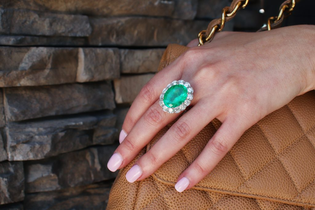 emerald ring with diamonds holding chanel bag