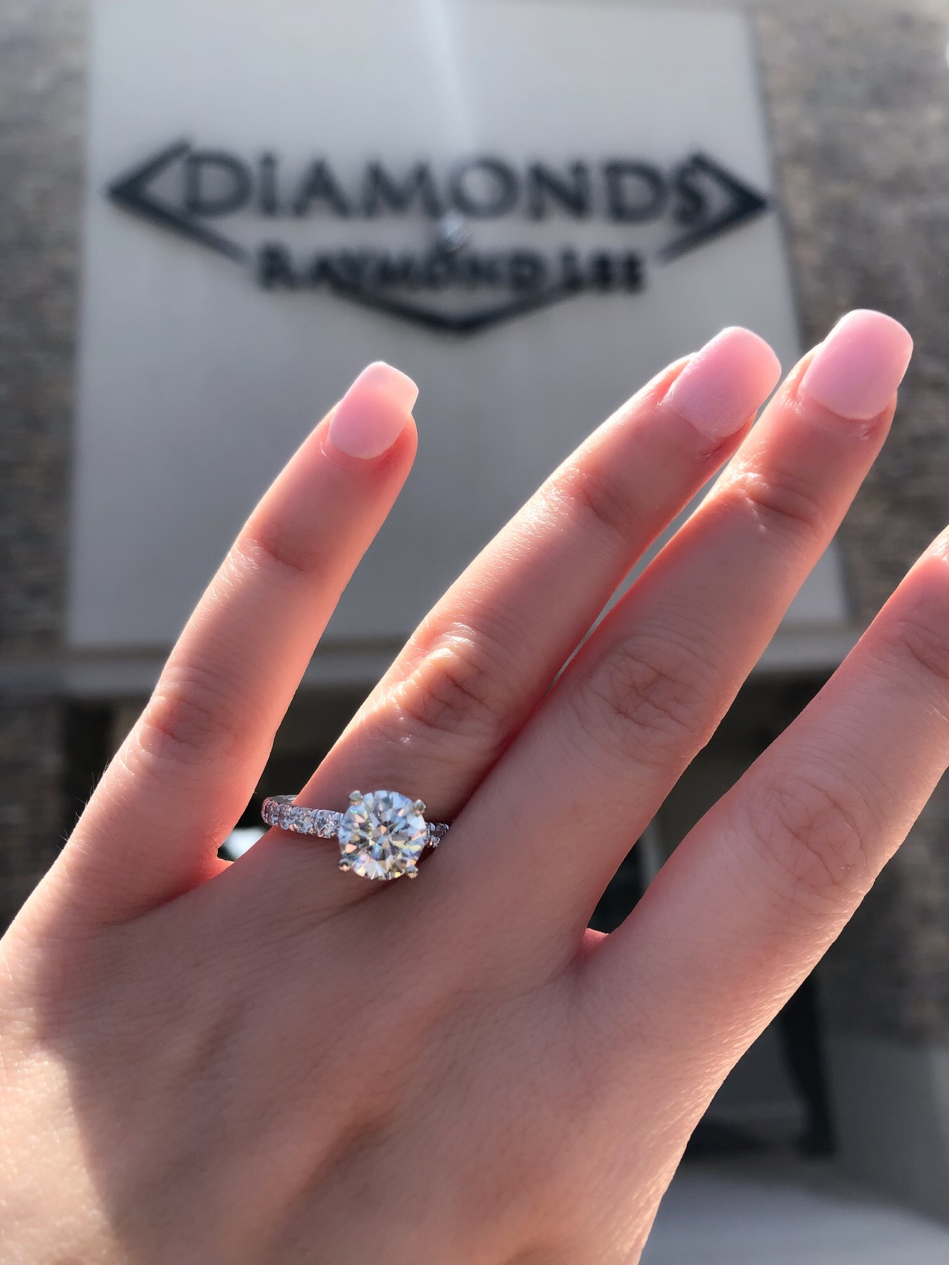 solitaire engagement ring in front of diamonds by raymond lee where you can find how much to spend on an engagement ring