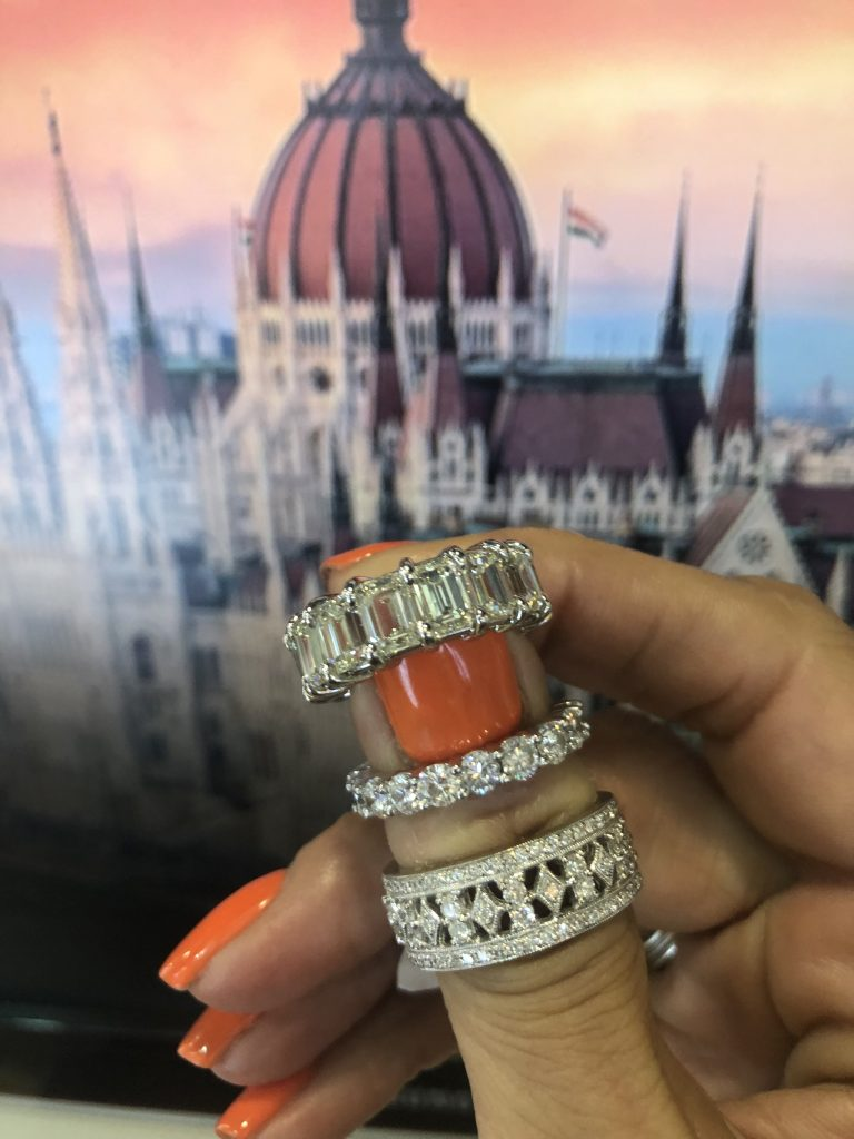 3 white eternity diamond band rings held up with image of Budapest in the background