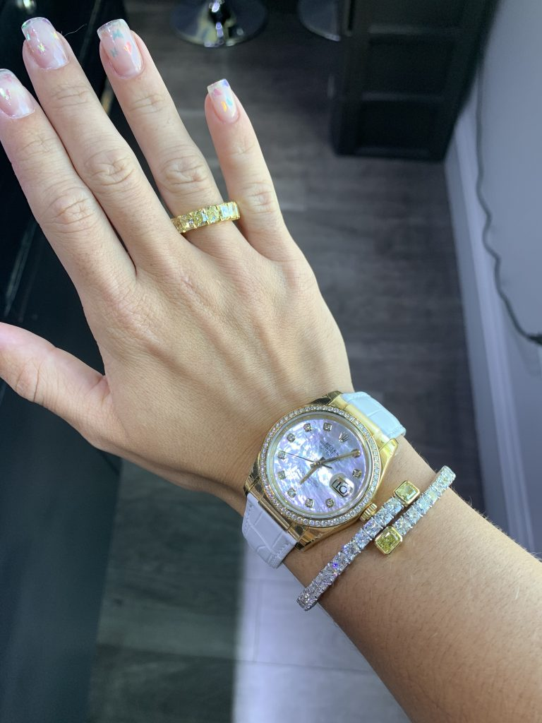 Rolex Oyster watch with white alligator strap worn with diamond ring and bracelet