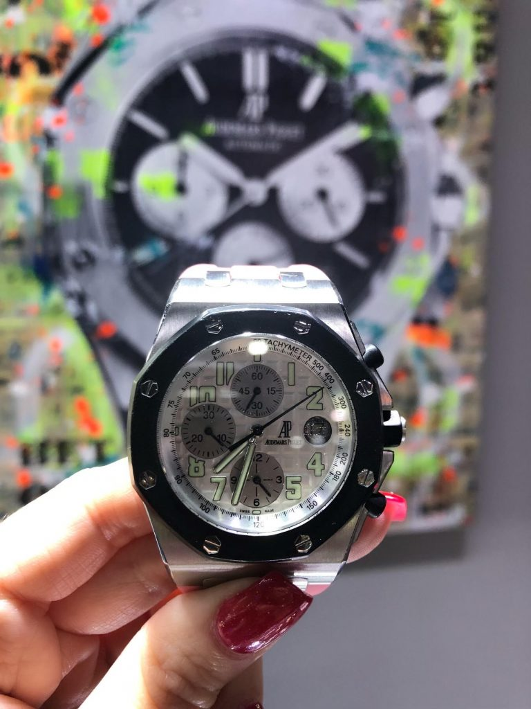 audemars piguet royal oak offshore held in front of painting