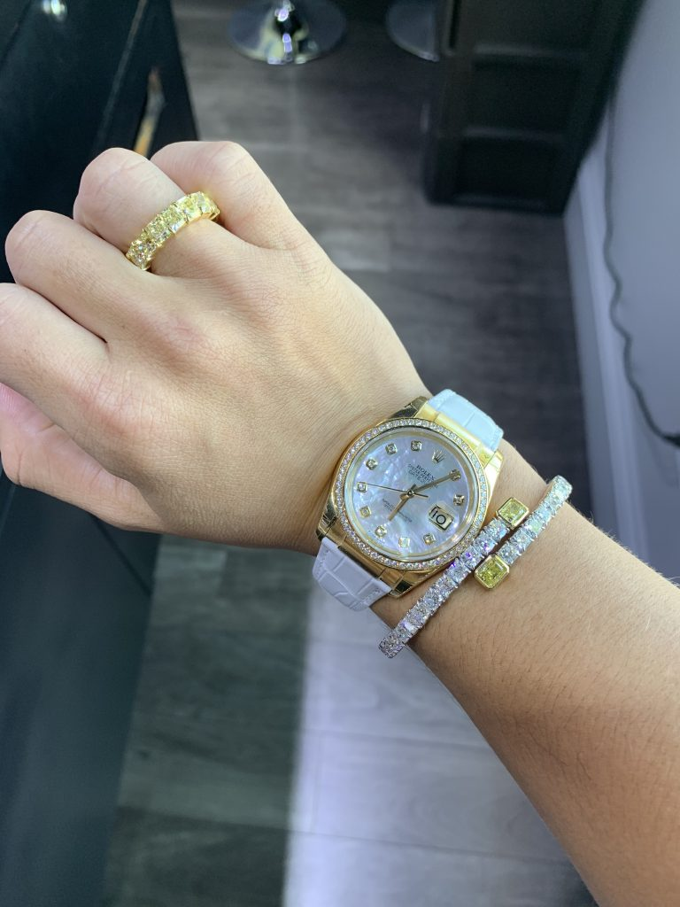 fine jewelry with mother of pearl Rolex watch on woman's wrist