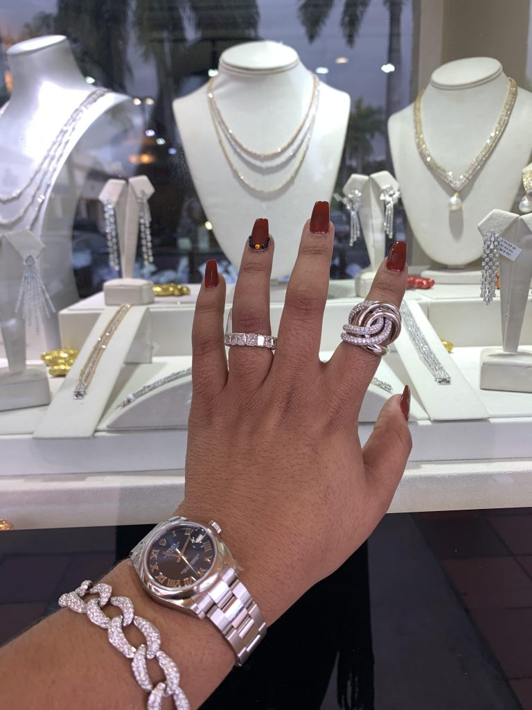 woman's hand reaching out to best jewelry 2019 in glass showcase