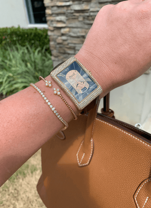 woman's arm with diamond watch and bracelets holding brown leather bag in front of boca jewelry store