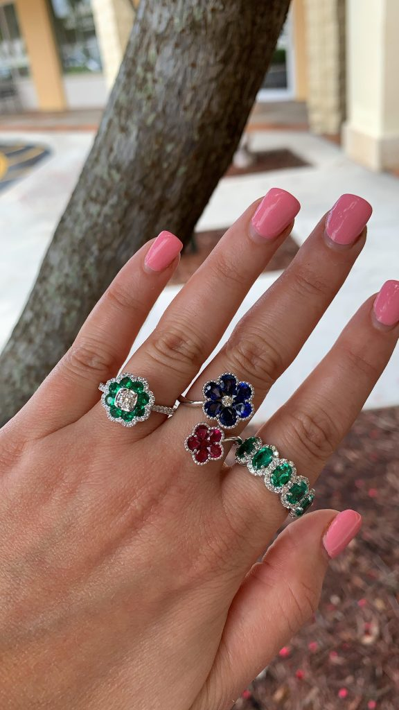 gemstone fine jewelry worn together emerald rings next to flower ruby and sapphire ring