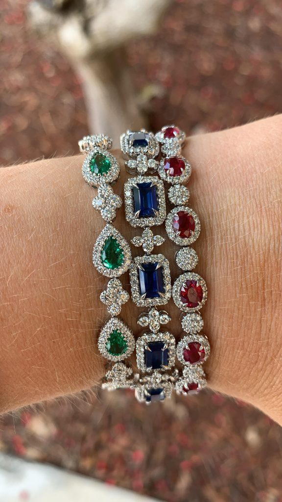 who buys gemstone jewelry feature three fine jewelry gemstone bracelets worn together emerald, sapphire, and ruby