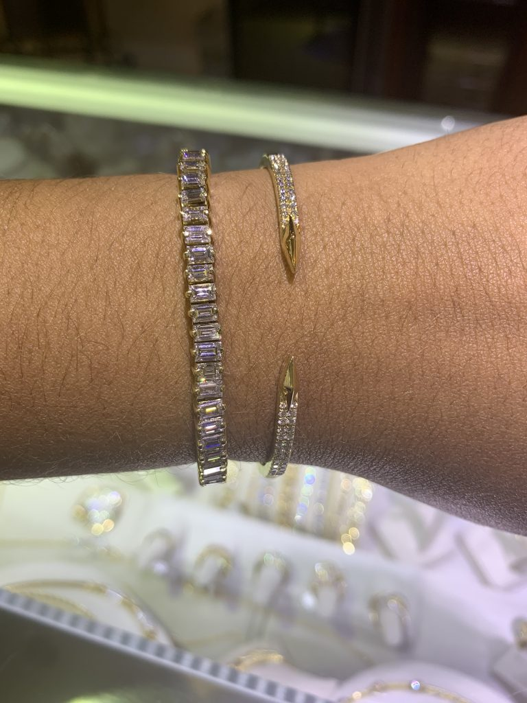 diamond bracelets showing why jewelry is the best gift in front of glass case of fine jewelry