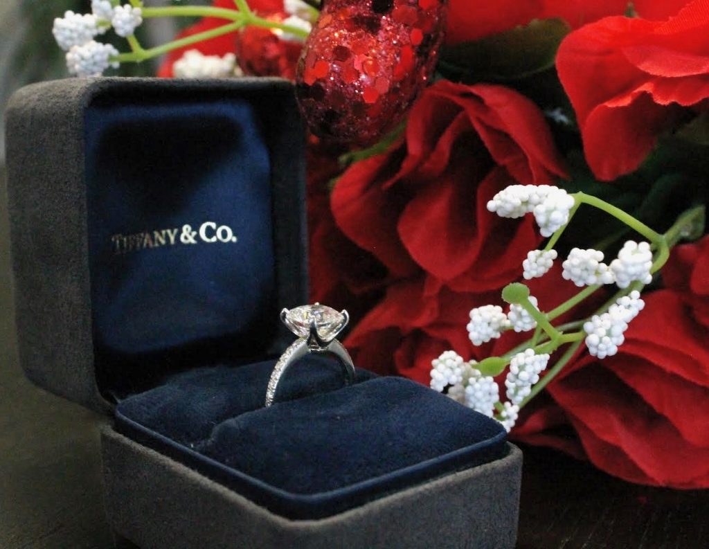 tiffany & co diamond engagement ring in box solitaire ring next to flowers